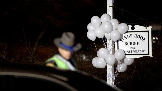 White balloons decorate the sign for the Sandy Hook Elementary School as a Connecticut State Trooper stands guard at the school's entrance (AP Photo/David Goldman)