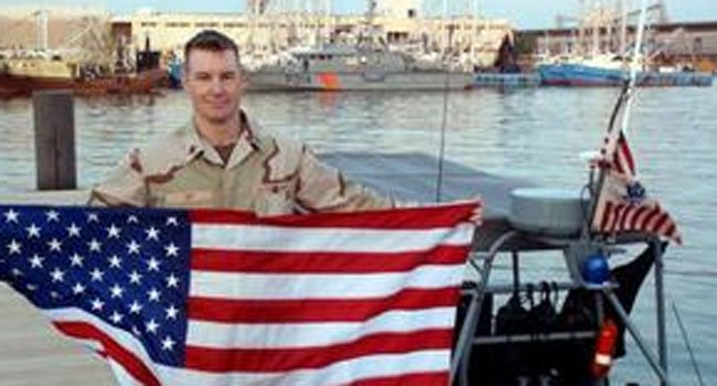 © The photo shows Officer Jonathan Ley holding an American Flag. (Courtesy of the Norwich Bulletin)