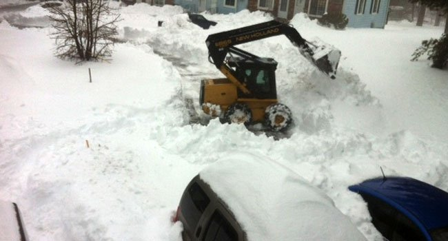© Crews clear snow from a home after three days.