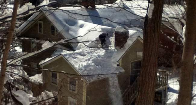 © Man is clearing snow off a roof.