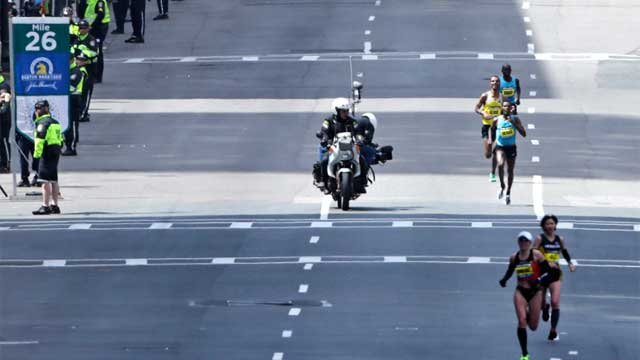 A motorcycle camera crew photographs the lead men's finishers as they pass the 26th mile marker, which was dedicated to the victims of the Sandy Hook Elementary School shooting in Newtown, during the 2013 running of the Boston Marathon. (AP Photo)