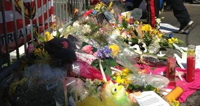 People leaving flowers and cards at edge of crime scene in Boston. FBI is working on other side of barricade.