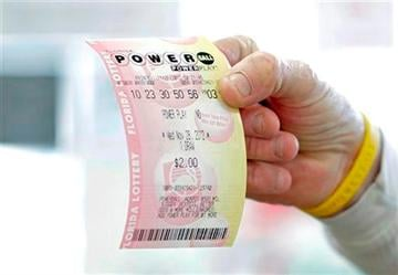 (AP Photo/Chris O'Meara, File). FILE - This Nov. 28, 2012, file photo shows a customer at a 7-Eleven convenience store with a Powerball ticket in Tampa, Fla.