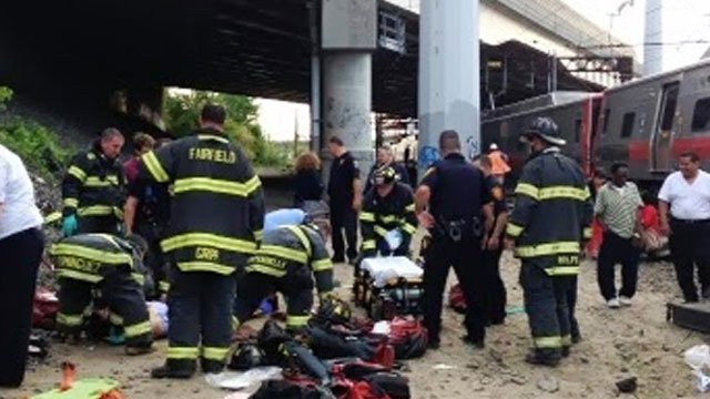 Firefighters attend to people injured during train derailment Friday night.