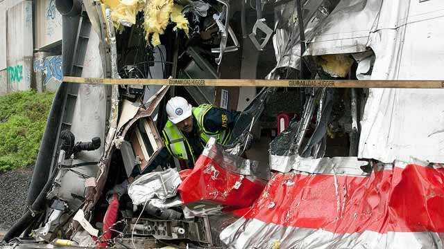 An investigators with the NTSB inspects damage.