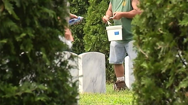 Public works crews clean up gravestones at Hillstown Road Cemetery.