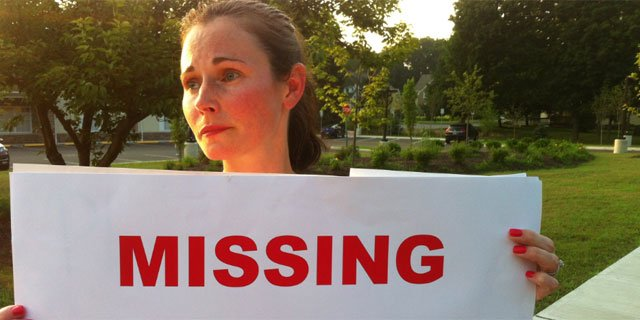 Mother Jessica Lyon holds up signs of her missing daughter Juliette.