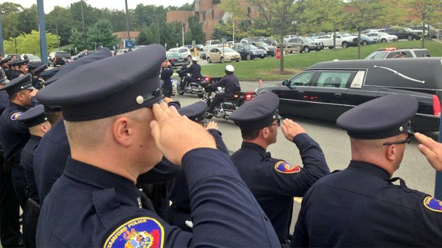 Police salute as the casket of Staff Sgt. Todd J. Lobraico Jr. goes by.