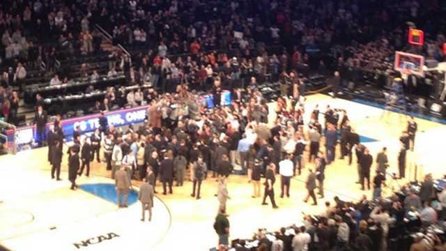 UConn players and members of the media flood the court at MSG after the Huskies win. (Photo Courtesy: Eric Parker)
