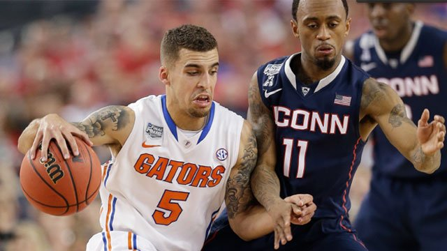Florida guard Scottie Wilbekin, left, drives past Connecticut guard Ryan Boatright during the first half. (AP Photo)
