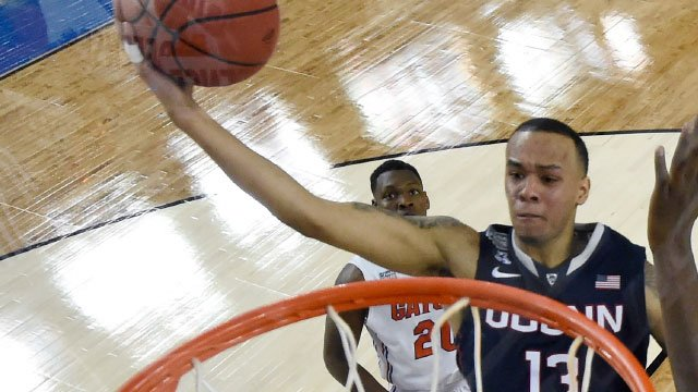 Connecticut guard Shabazz Napier (13) drives to the basket over Florida forward Dorian Finney-Smith. (AP Photo)