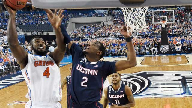 Florida center Patric Young (4) drives to the basket past Connecticut forward DeAndre Daniels (2) during the first half (AP Photo)