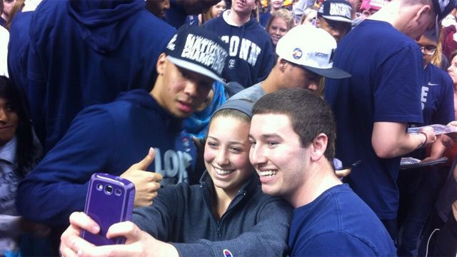 Fans fill Gampel Pavilion for championship rally to celebrate Huskies victory Selfies with Shabazz. Team circling Gampel greeting fans.
