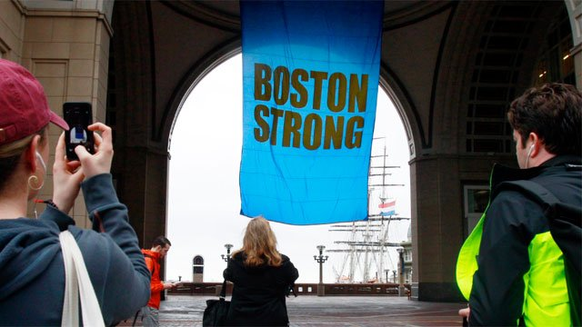 """People photograph a banner reading """"Boston Strong"""" as it hangs at Rowes Wharf on the first anniversary of the Boston Marathon bombings on Tuesday. (AP Photo/Bill Sikes)"""