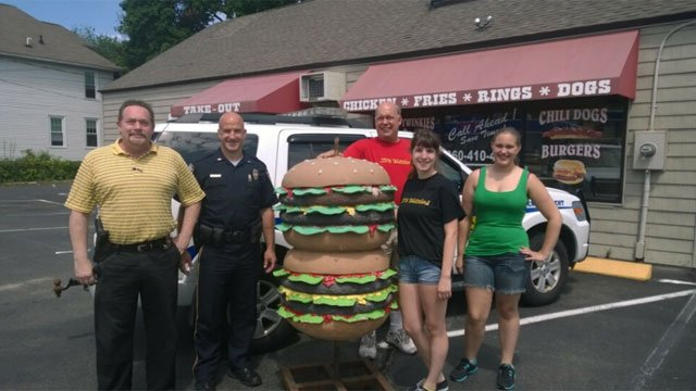 Big Steve's Grill owner and Plainville police pose for a photo after the stolen burger sign is returned to the Plainville restaurant. (Photo Courtesy: Ben Comparone)