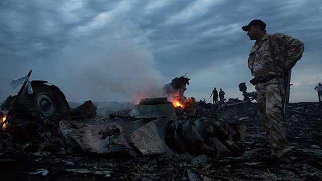 People walk amongst the debris, at the crash site of a passenger plane near the village of Grabovo, Ukraine, Thursday, July 17, 2014. A Ukrainian official said a passenger plane carrying 295 people was shot down Thursday as it flew over the country and pl