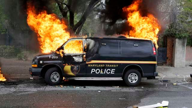 Baltimore police vehicle on fire during riots (AP Images)