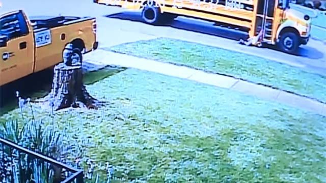 Surveillance cameras captured the terrifying moments when a 7-year-old girl was dragged alongside a school bus. (CBS News)
