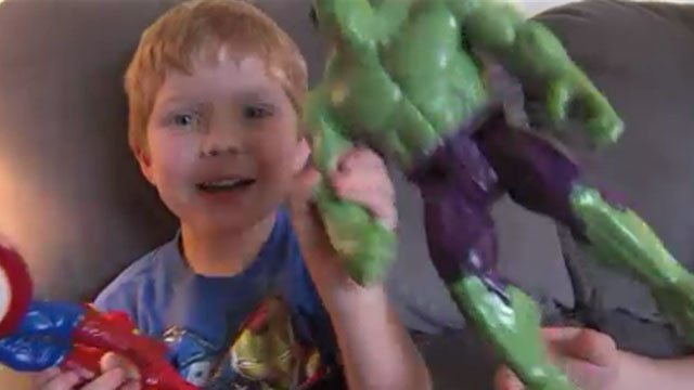 Kyler Livingston shows off his superhero action figures. (CNN)