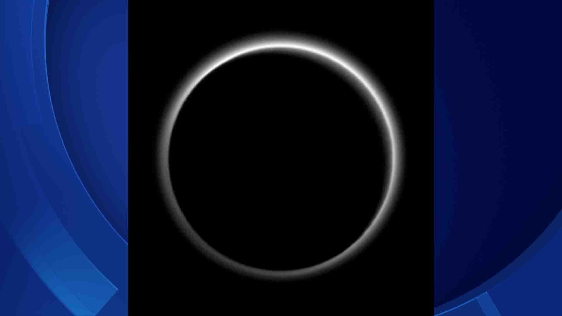 Backlit by the sun, Pluto's atmosphere rings its silhouette like a luminous halo in this image taken by NASA's New Horizons spacecraft around midnight EDT on July 15. (NASA photo)
