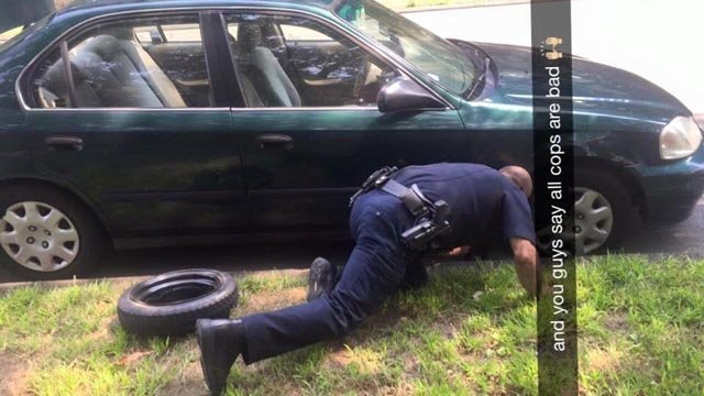 Sgt. Paul Scarcella changes a flat tire. (Hamden police Facebook photo)