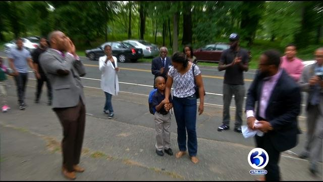 A group of men from Hartford cheered on students as they returned to Martin Luther King Jr. Elementary School. (WFSB)