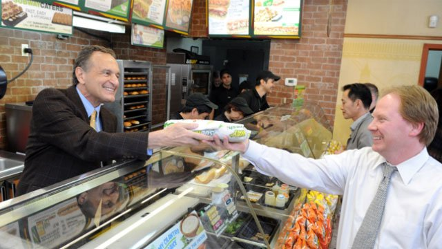 Fred DeLuca, left, Co-Founder and CEO, SUBWAY Restaurants, hands a customer their sandwich at a SUBWAY store in New York, Tuesday, May 6, 2014. (Diane Bondareff/Invision for SUBWAY/AP Images)