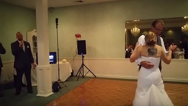 "Kelly Meadows dances with her father while her husband, Andrew, signs ""Your Daddy's Boots"" by Dustin Lynch. (YouTube)"