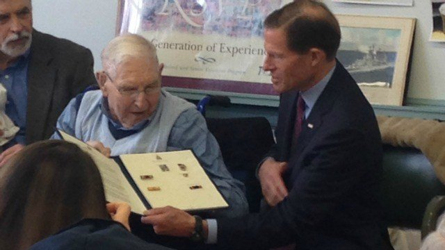Fred Carlage, of Woodstock, receives his medal from U.S. Sen. Richard Blumenthal. (WFSB)