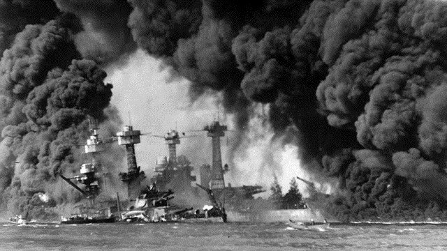The U.S. Navy battleships USS West Virginia (BB-48) (sunken at left) and USS Tennessee (BB-43) shrouded in smoke following the Japanese air raid on Pearl Harbor. (National Archives and Records Administration photo)